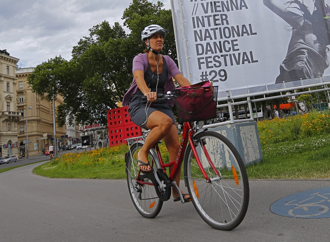 A woman rides a bicycle past a sign advertising the 29th Impulstanz Festival in Vienna on July 11, 2012. Dance in all its forms, from performances to workshops, lectures and parties, takes over Vienna for a month starting on July 12, 2012, as the Austrian capital welcomes the 29th Impulstanz Festival. AFP PHOTO / ALEXANDER KLEIN        (Photo credit should read ALEXANDER KLEIN/AFP/GettyImages)