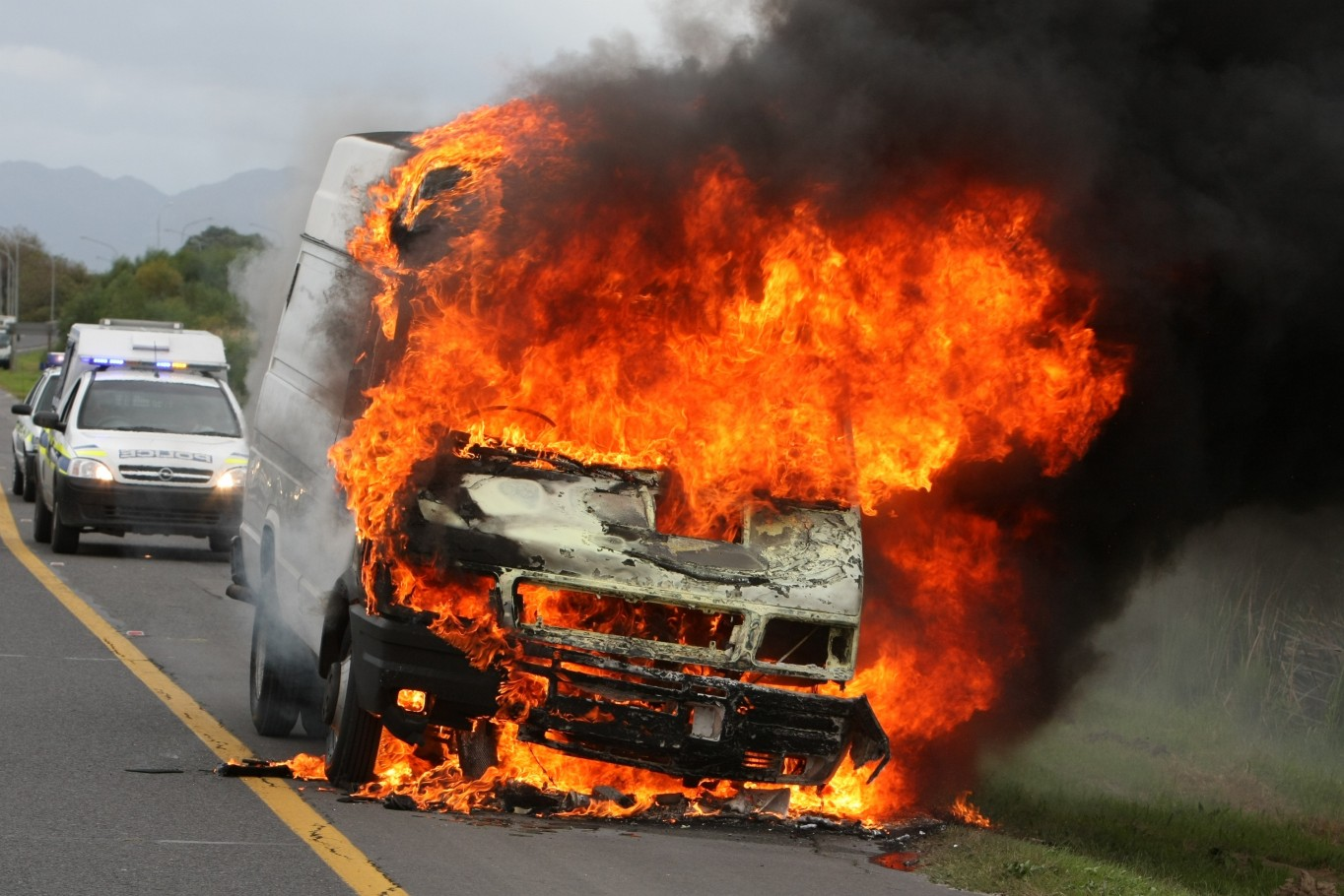 12392343 - delivery type vehicle on side of road burning with large flames and smoke and police cars in background