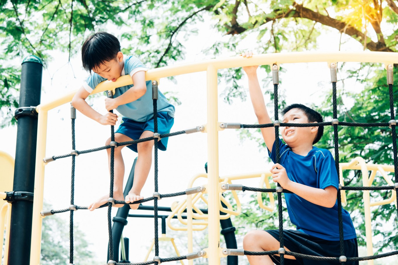 Vintage color tone, Young asian boy climb on the black rope fence and yellow bar by his hand to exercise at out door playground under the big tree.