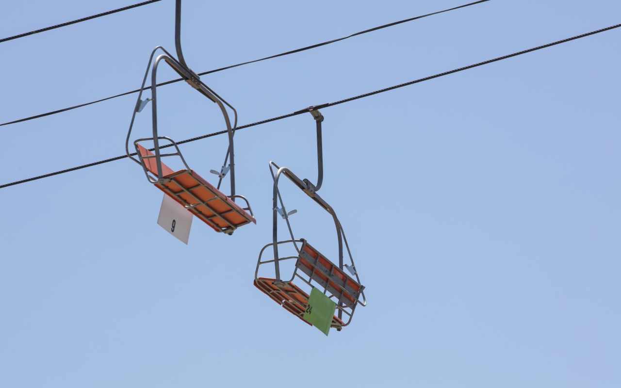 Orange chairlift at an amusement park running on steal cables