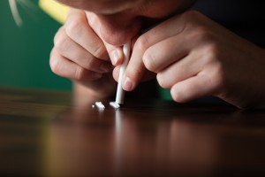 Addicted young boy sniffing crystalline cocaine laid out in rows on a table using a straw to snort it into his nostril in a concept of drug abuse