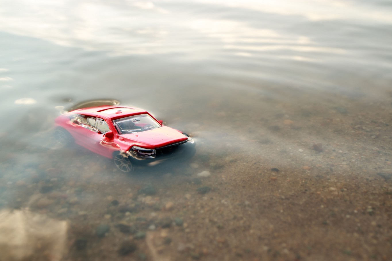 red toy car submerged in the water, drowned in the pond facing us, the accident in the summer on the beach